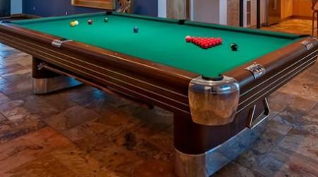 "Restored ""The Anniversary"" billiard table with gleaming corner pockets and legs"
