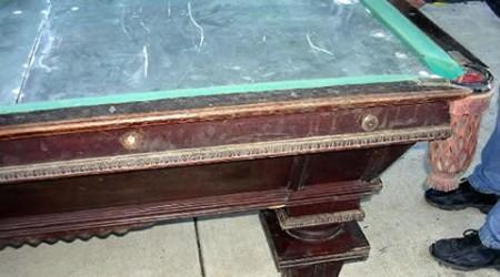 Prior to restoration, a National II antique billiards table