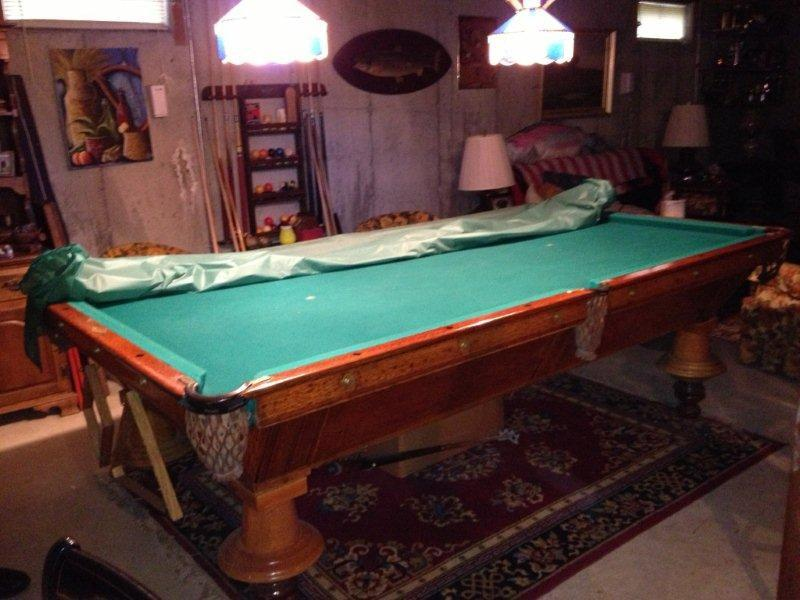 Damaged antique pool table with upside down legs